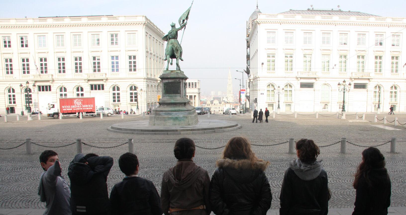 leerlingen kijken naar het standbeeld van Godfried van Bouillon op het Koningsplein richting Kunstberg